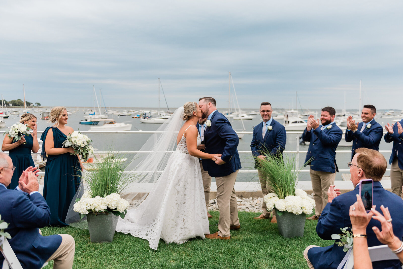 first kiss at a wedding ceremony on the lawn at the duxbury bay maritime school waterfront venue