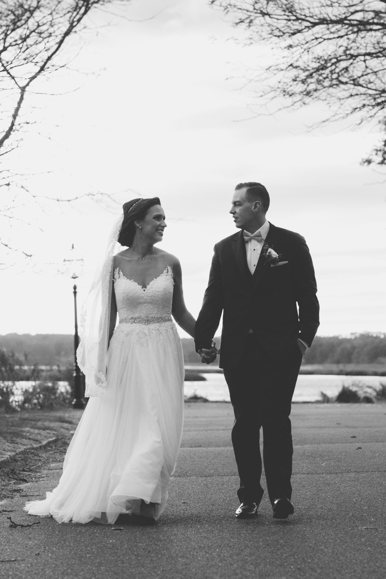 black and white photo of bride and groom holding hands and walking from wedding at Three Village Inn