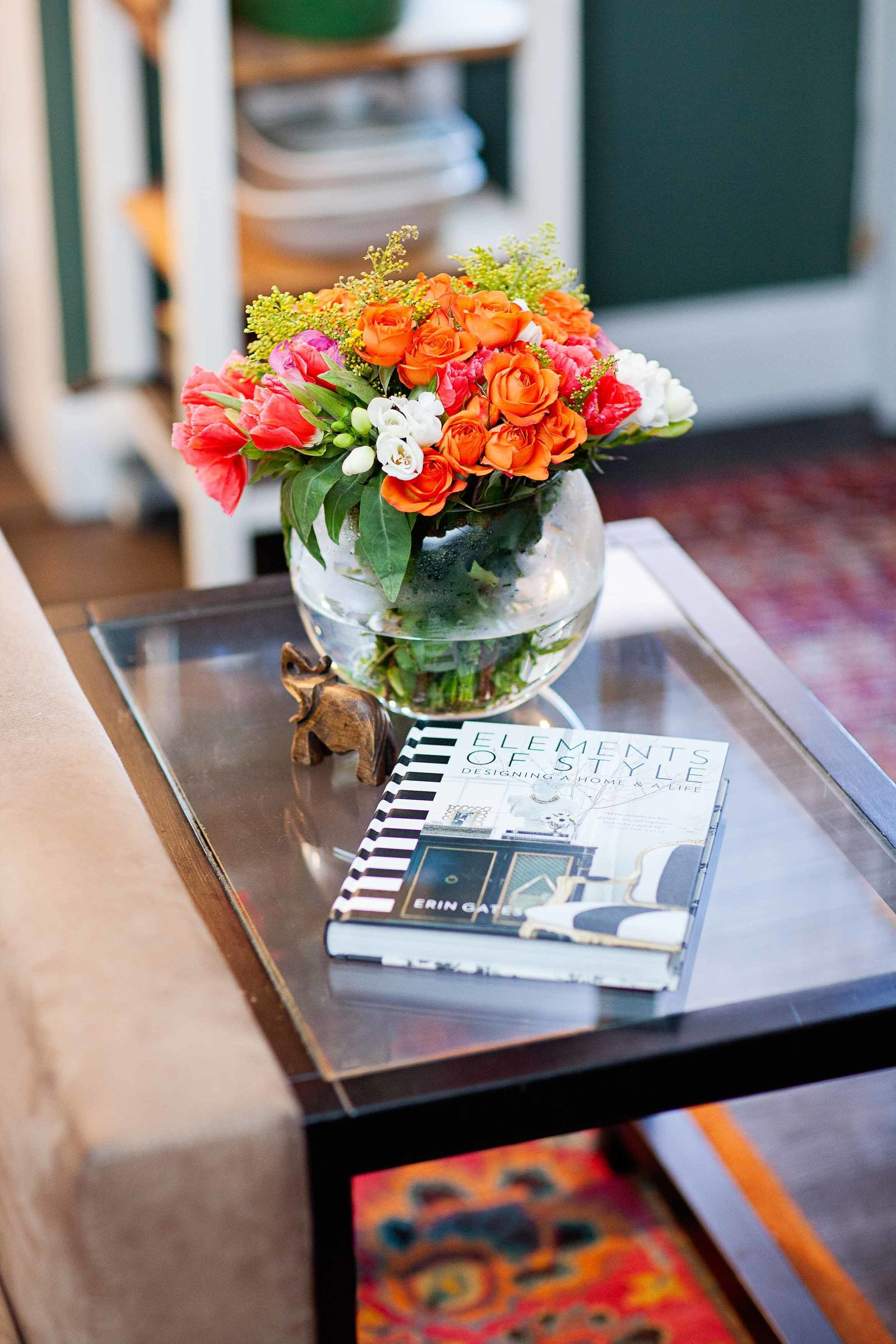 A glass end table with a book and fresh flowers.