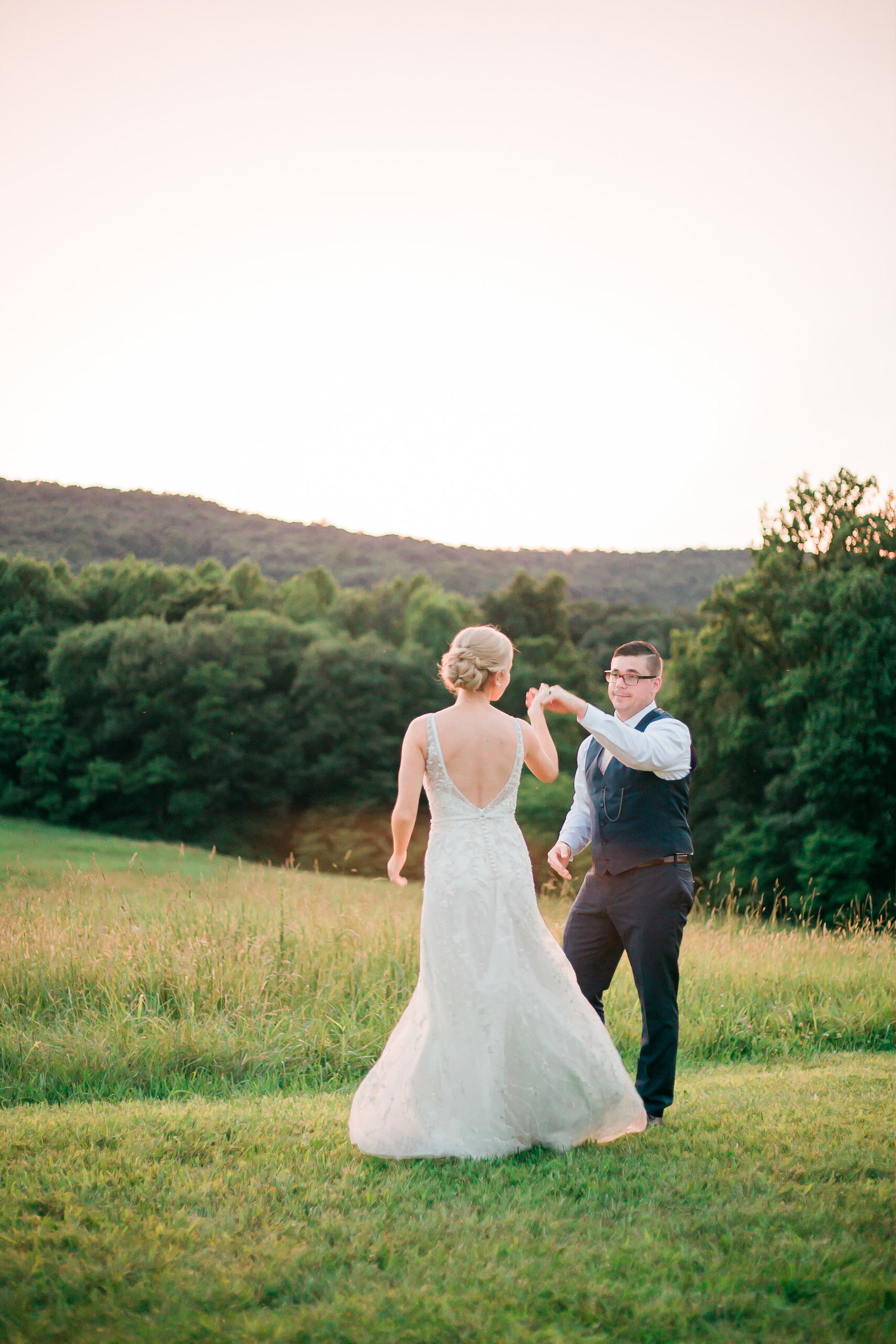 Bride and groom dance in a golden field at Springfield Manor Maryland