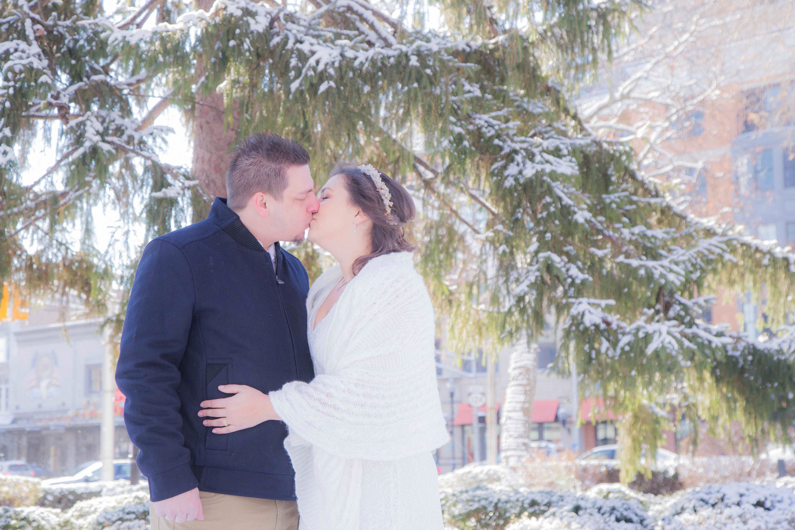 Bride and groom kiss in park while snowing on their elopement day.