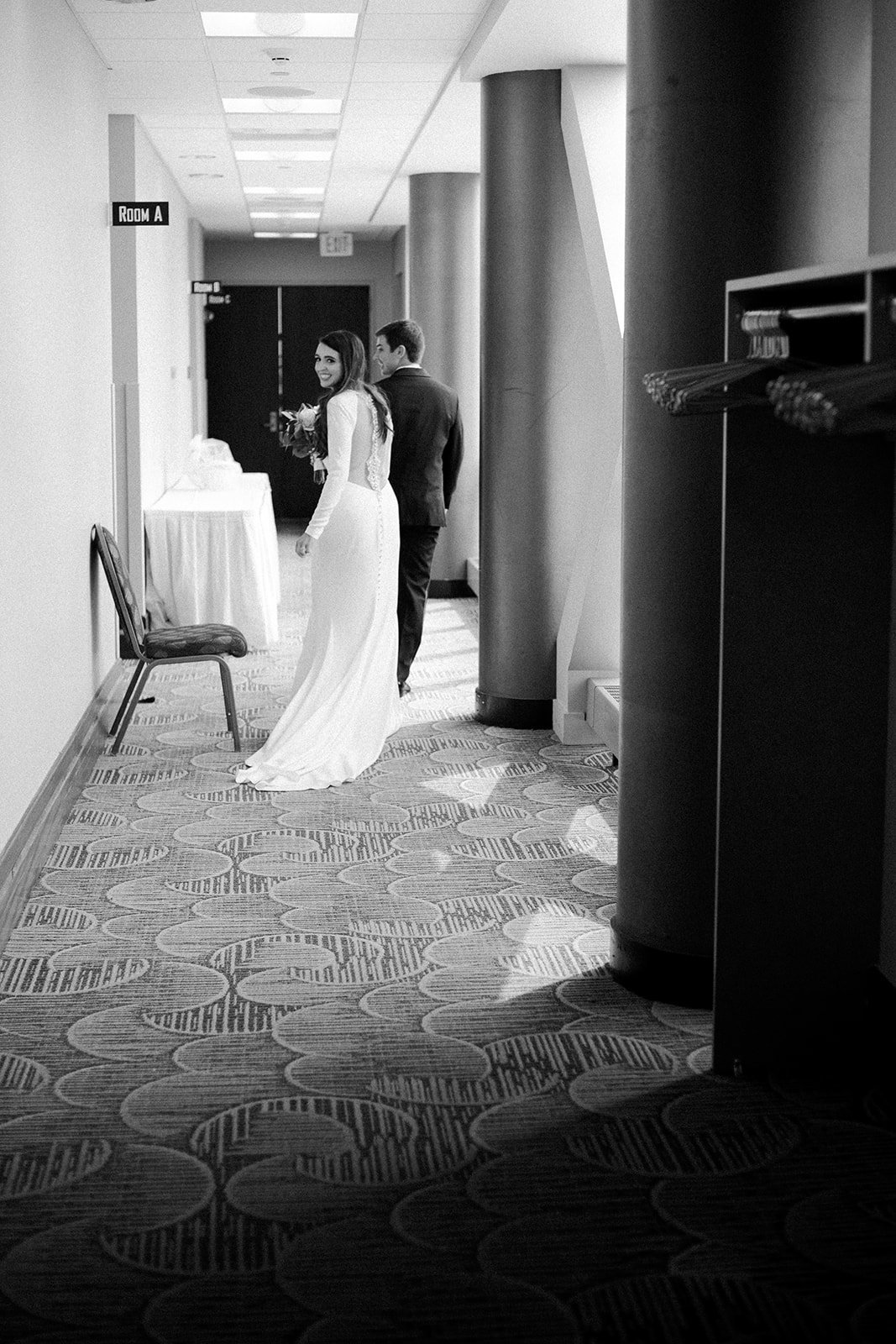 Bride and groom sneaking down a hallway with bride smiling back at camera during their Minneapolis wedding day