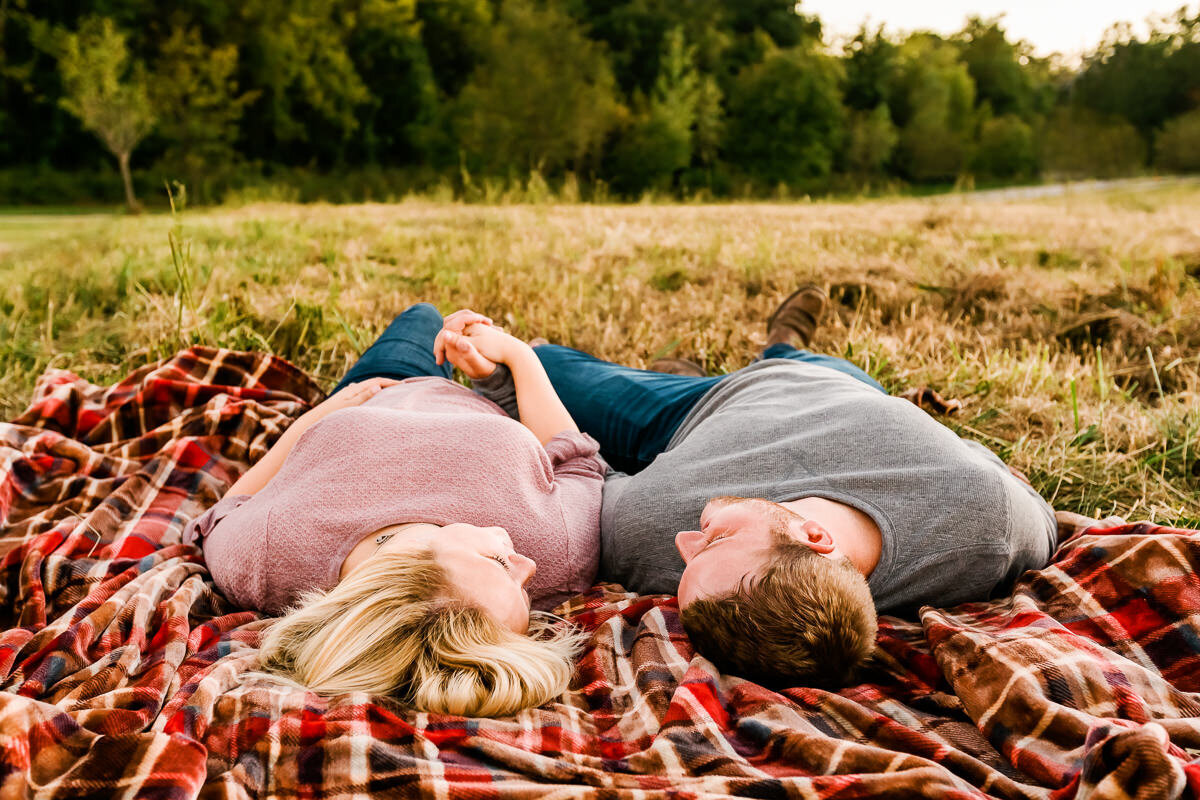 Couple holding hands looking at each other while they lie on a blanket in a Kansas City park.