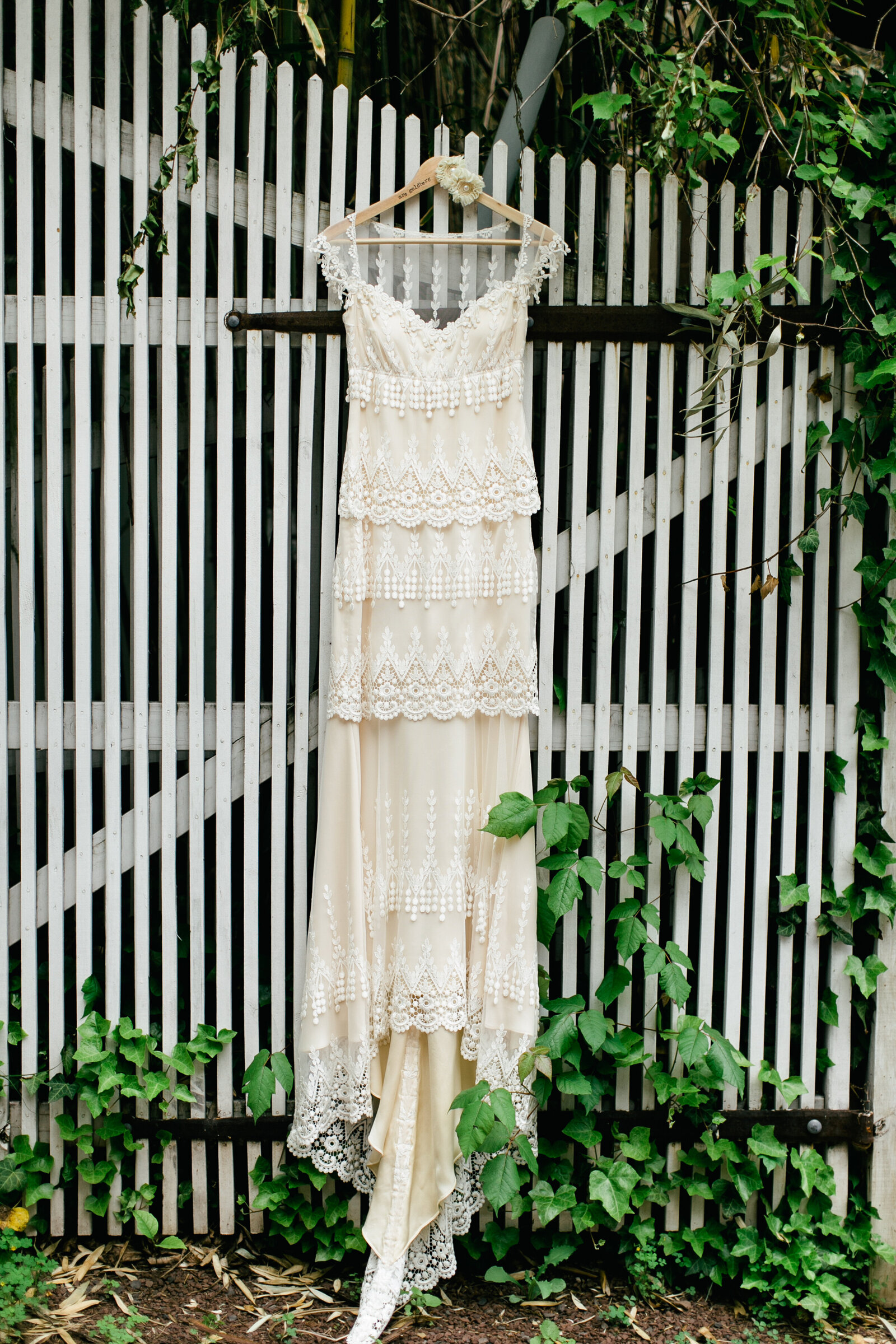 brides lace wedding dress hanging outside