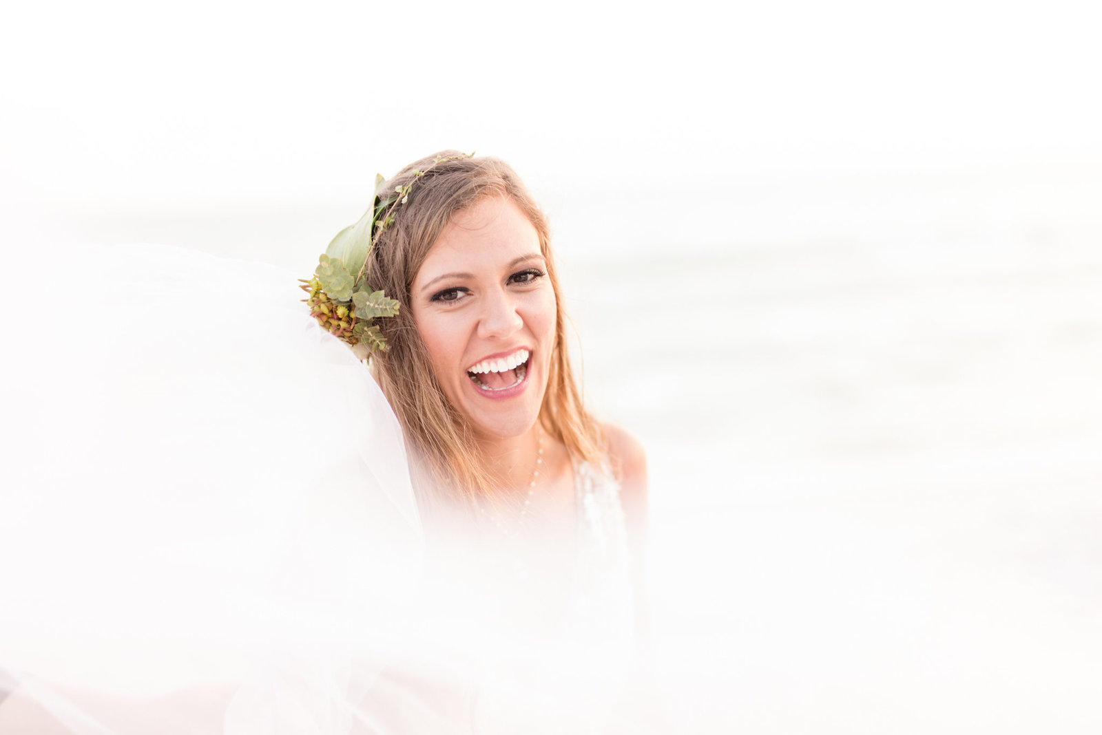 Tampa bride laughs while veil blows in front of her.
