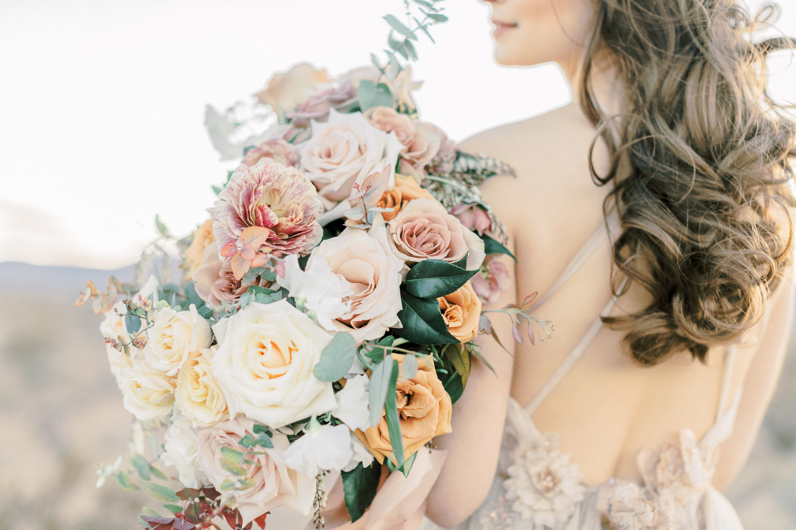 photo of a bride holding a bridal bouquet with ivory, peach and pink colors in the Las Vegas desert