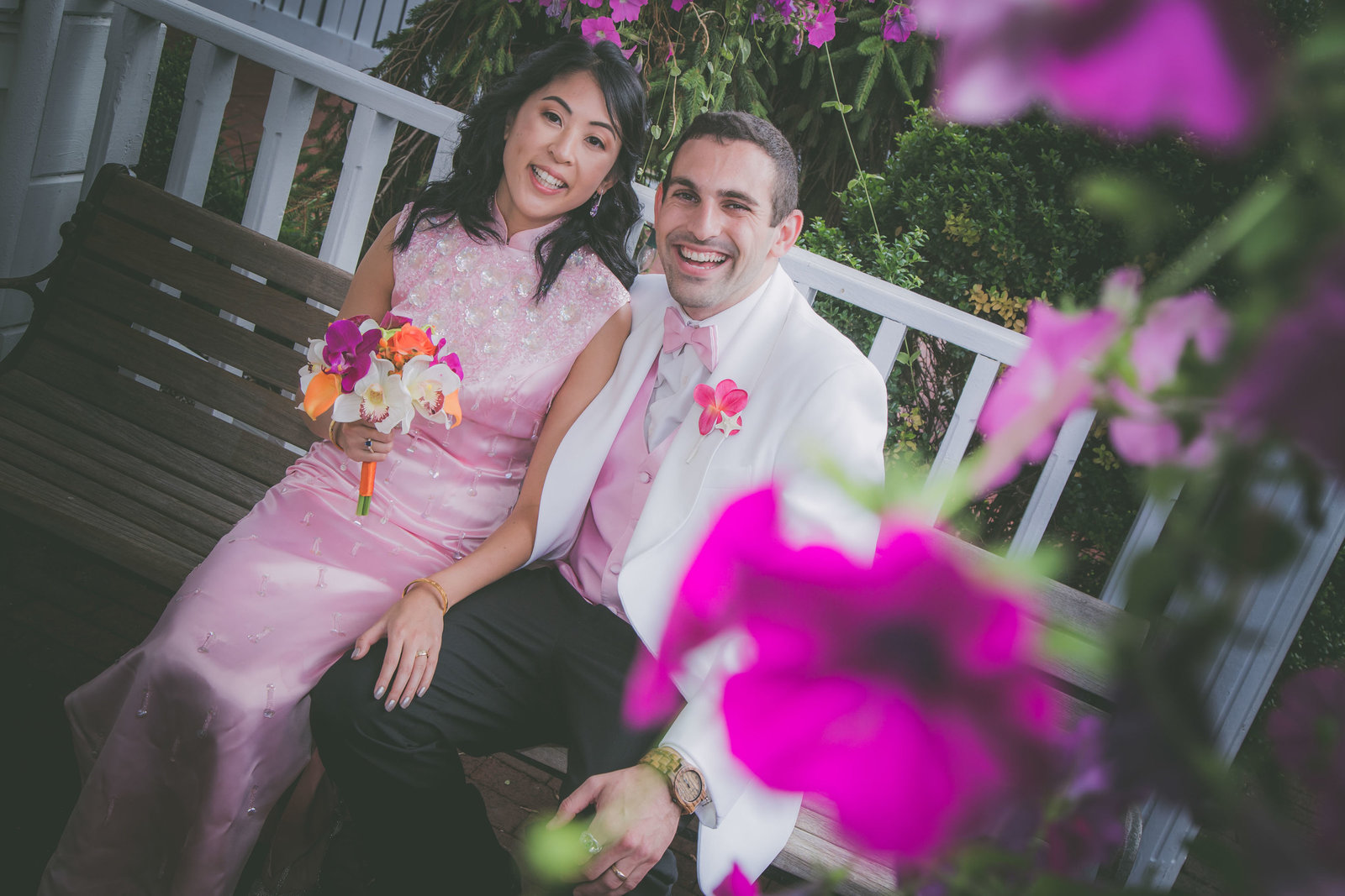 Couple looks at photographer and is framed in pink flowers.