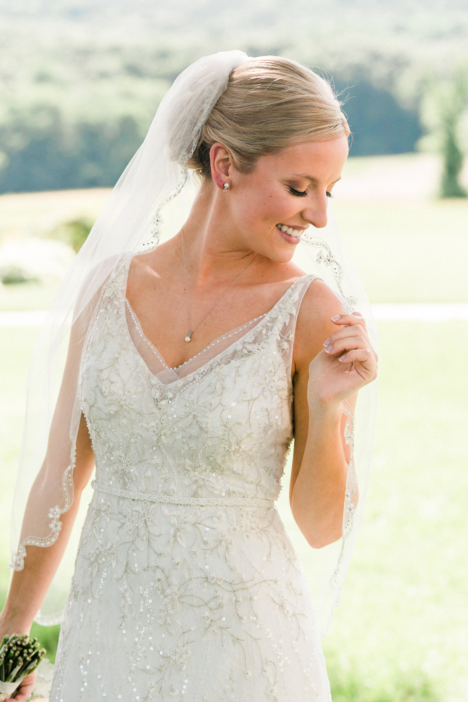 Close up of a bride in a beaded wedding dress smiles for her bridal portrait