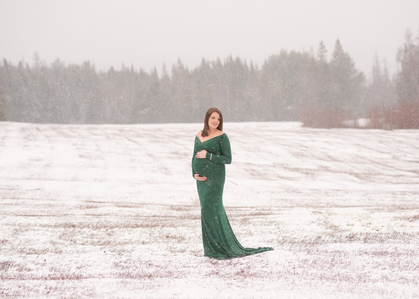 winter maternity session of a woman wearing a green gown in a snowing field
