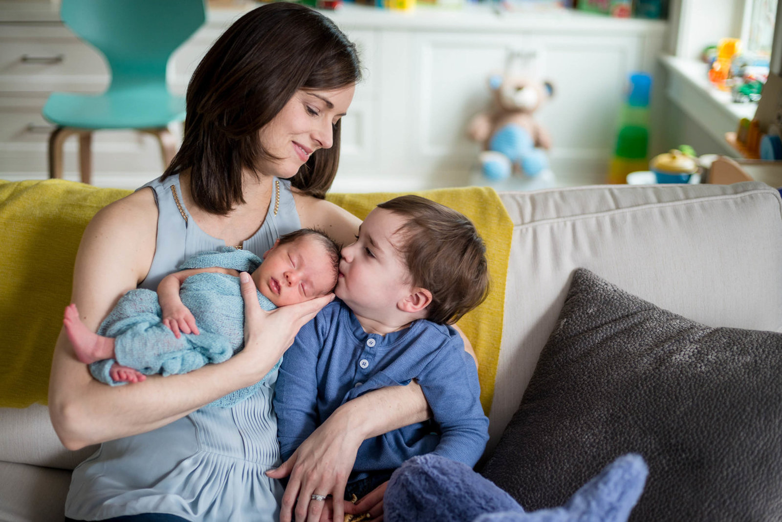 Brother kissing newborn head with mom holding baby at home lifestyle session