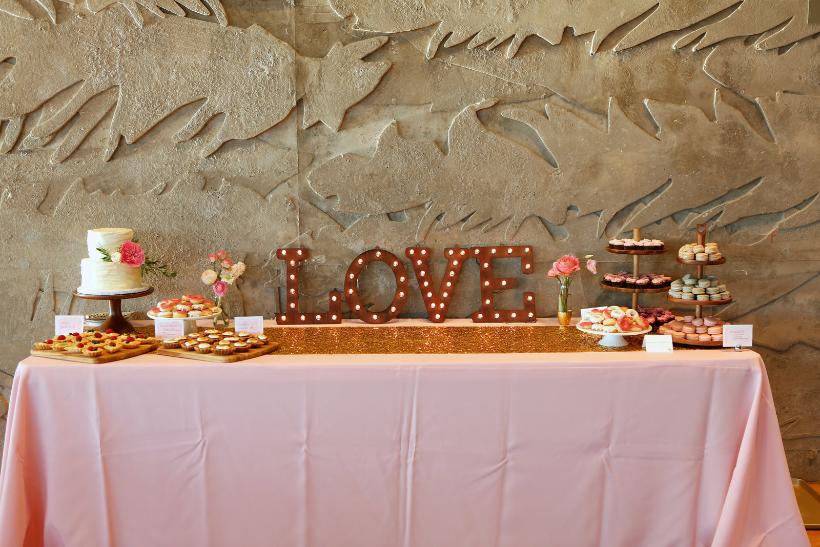 mini dessert bar with donuts cake and tarts during a wedding reception