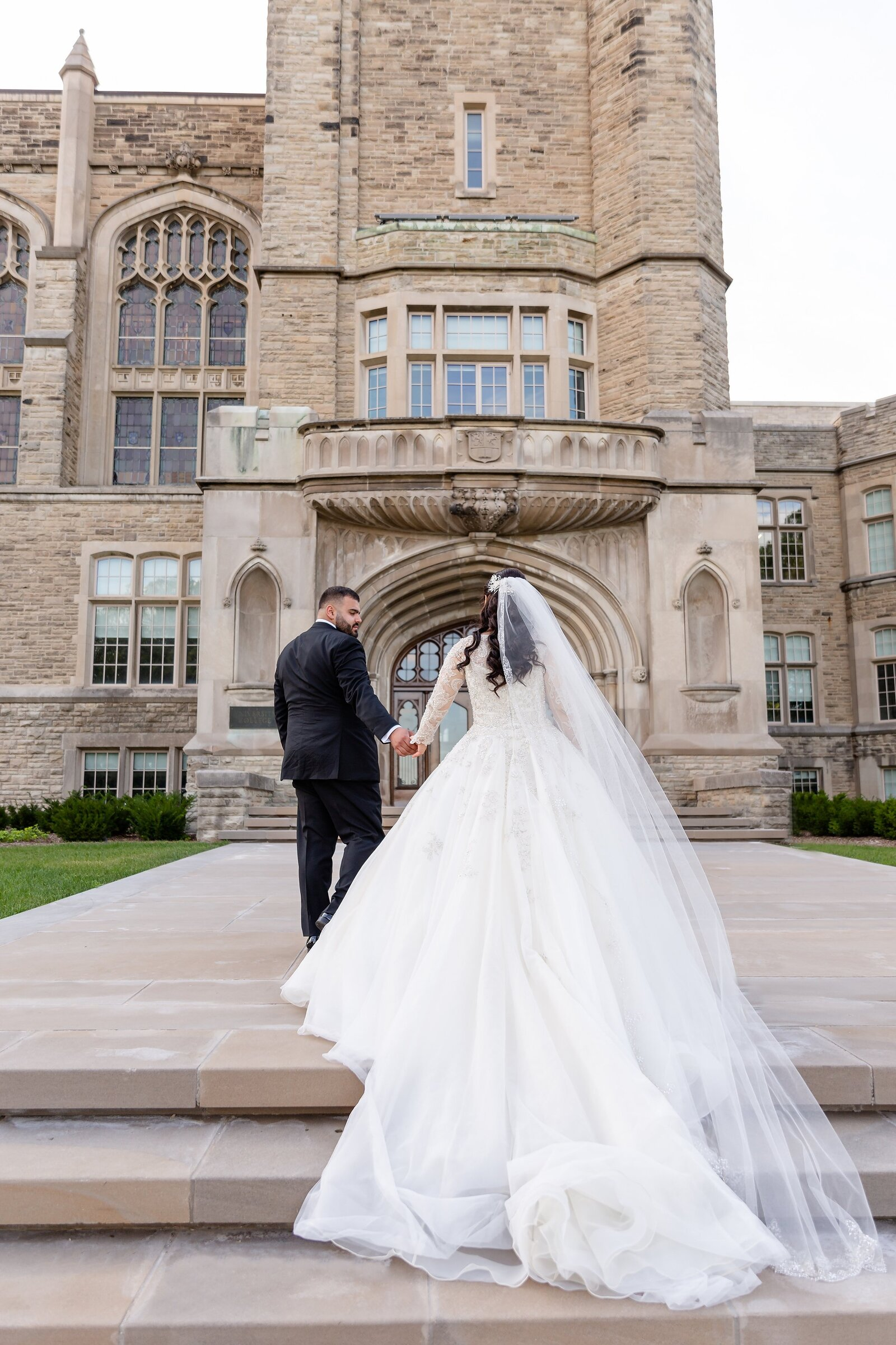 Groom-leads-his-lebanese-bride-up-the-steps-at-western-university-during-their-wedding