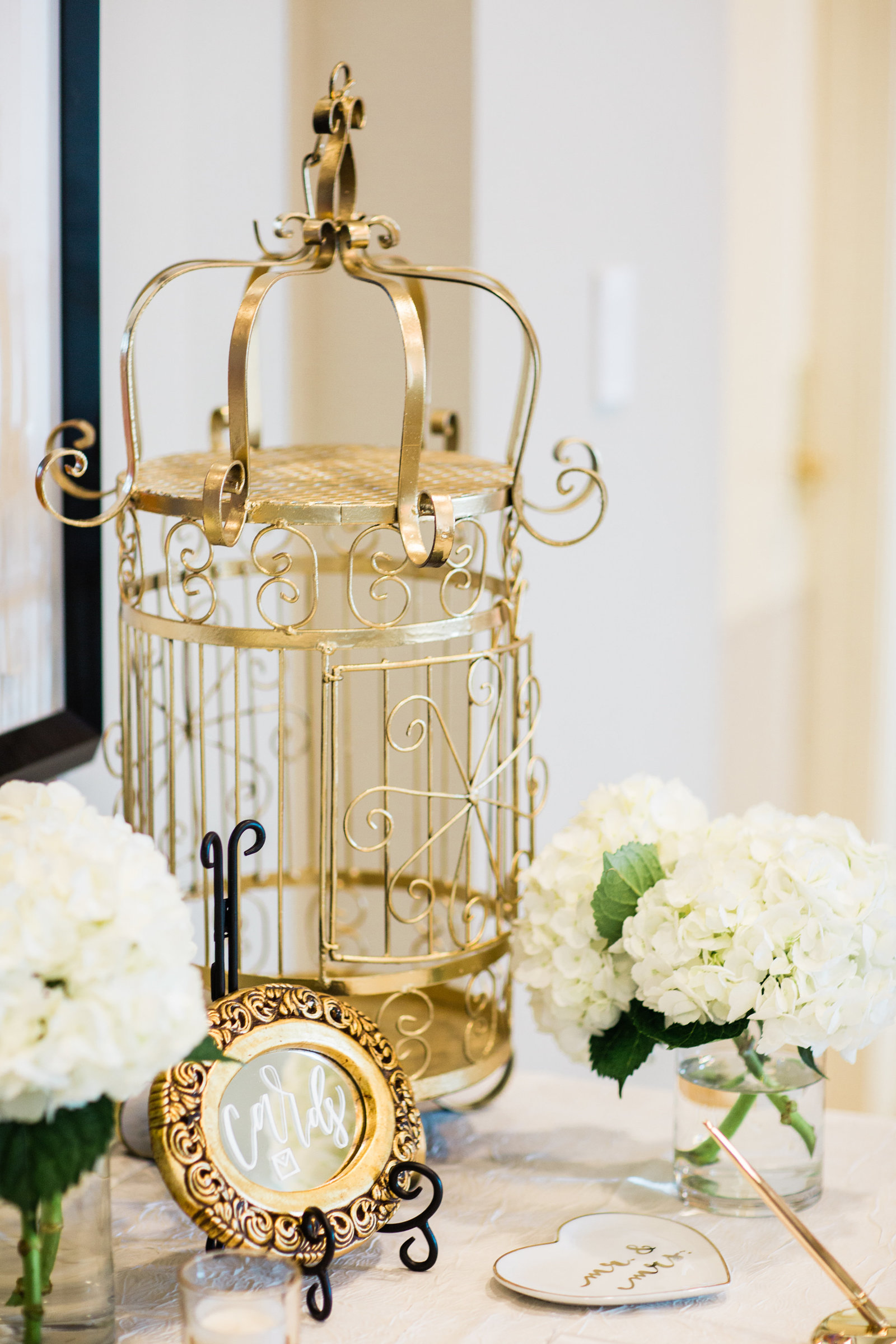 gold birdcage and white blooms accenting escort card table