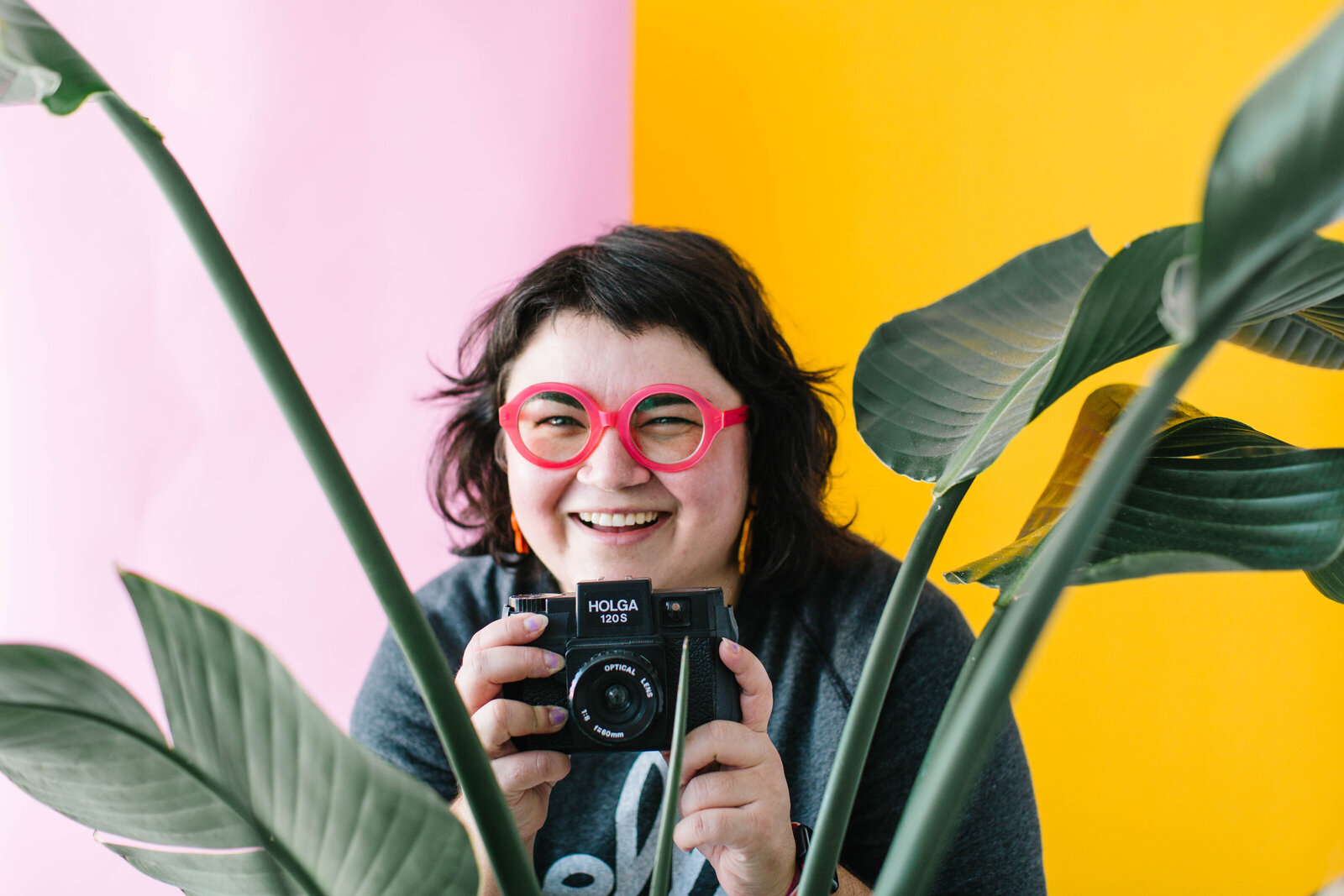 photo of photographer in red round glasses hiding in bushes in front of pink and yellow backdrop