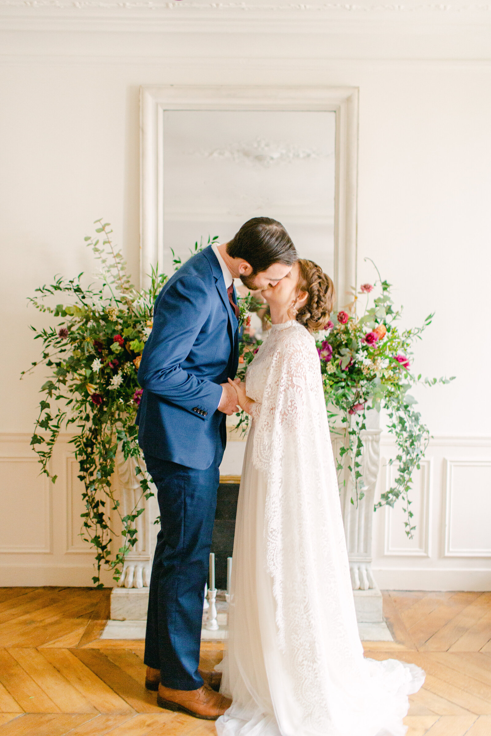 bride and groom kiss in front of fireplace mantel in paris apartment