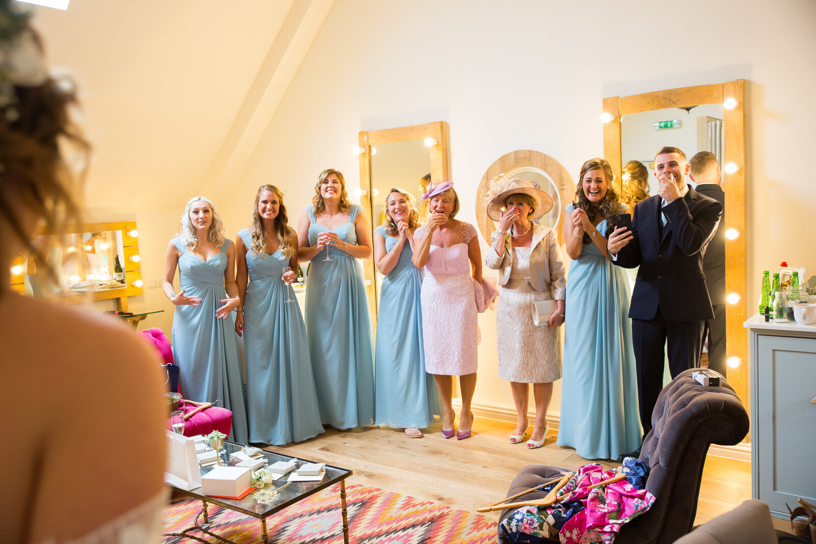 Wedding photography of bridesmaids seeing bride in wedding dress for the first time at Millbridge Court Surrey. Photography by Lynsey Grace Photography