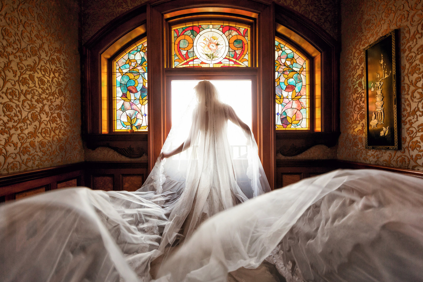 bride in front of stained glass window with wedding dress flowing at newhall mansion