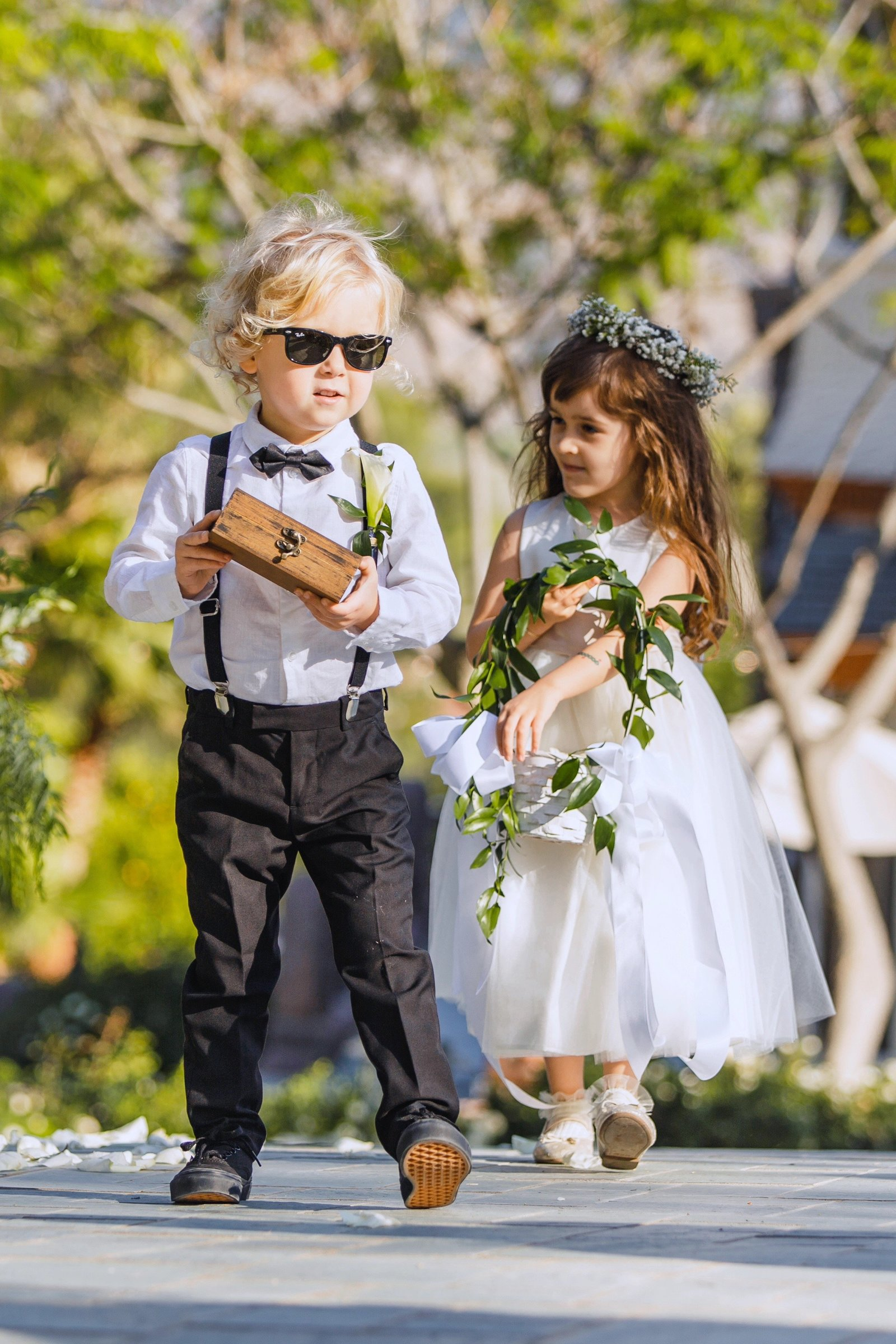 ring bearer and flower girl walking down the aisle at the epic newhall mansion