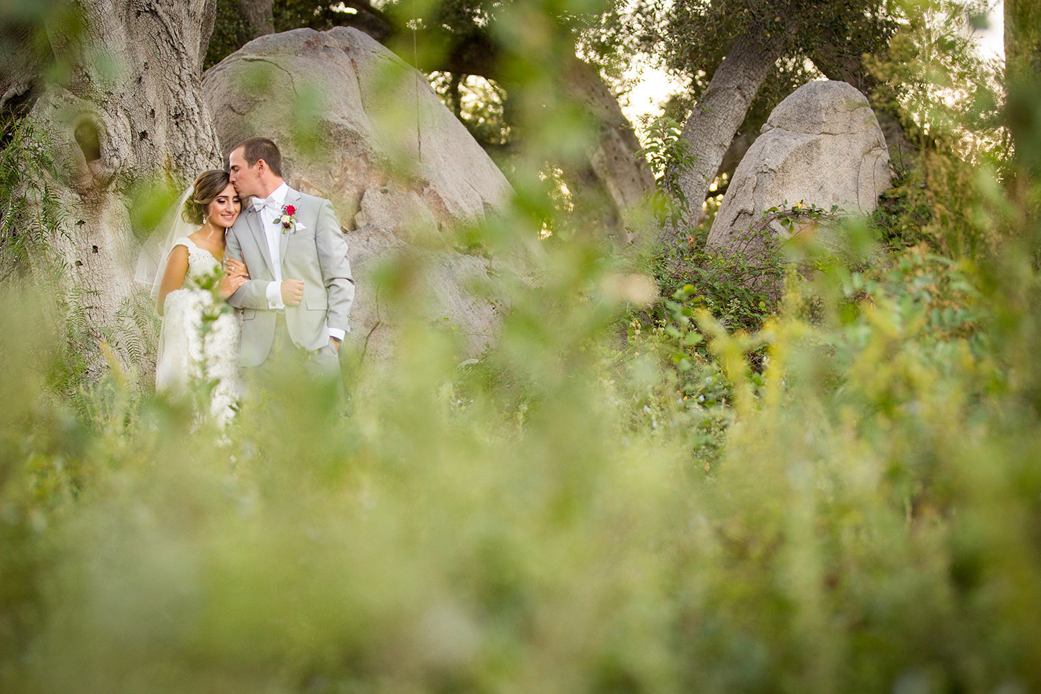 bride and groom kissing in a open field