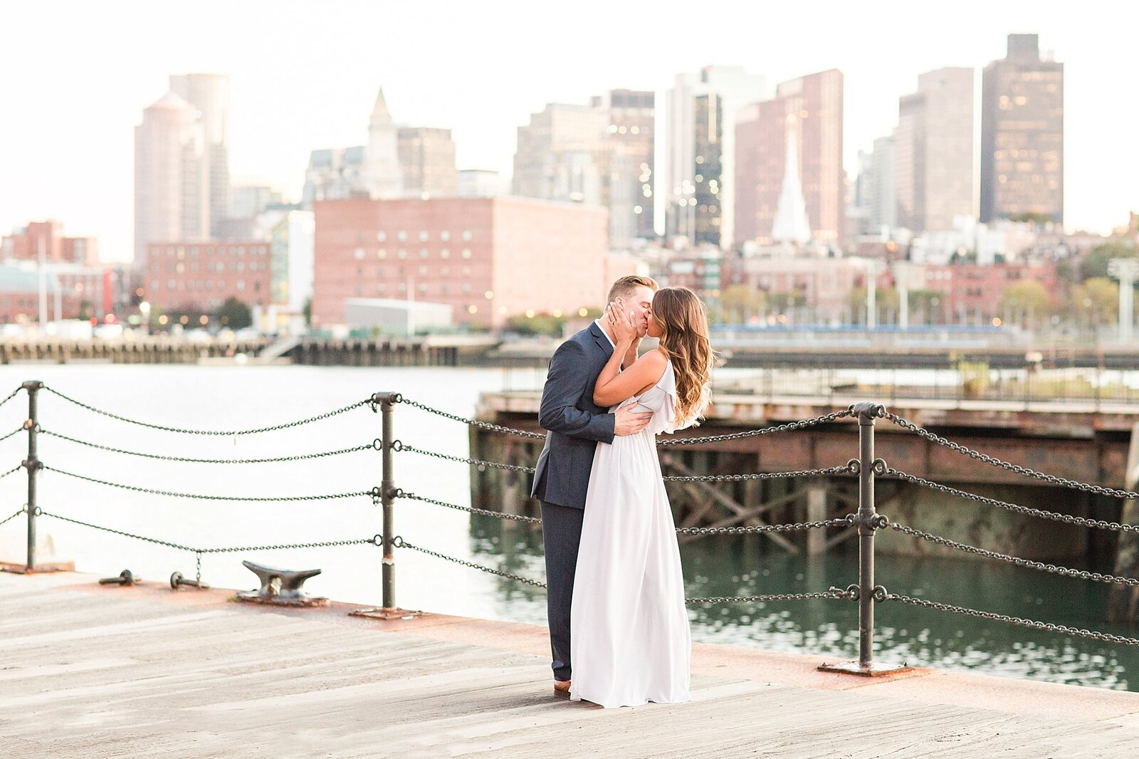 man and woman kissing with Boston skyline in background
