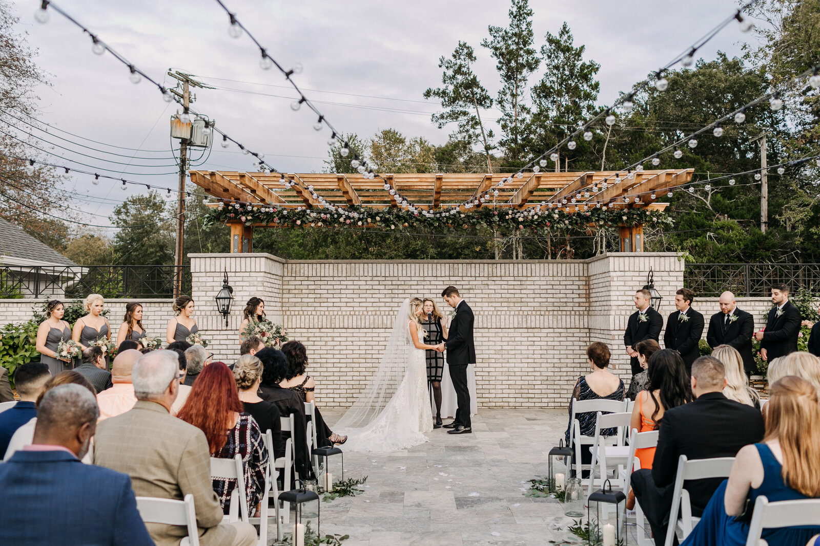 outdoor wedding ceremony with brick wall string lights