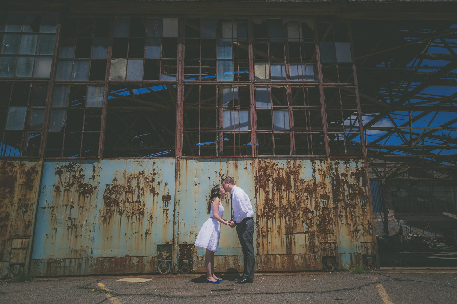 Couple kisses against rusty airplane hanger background.