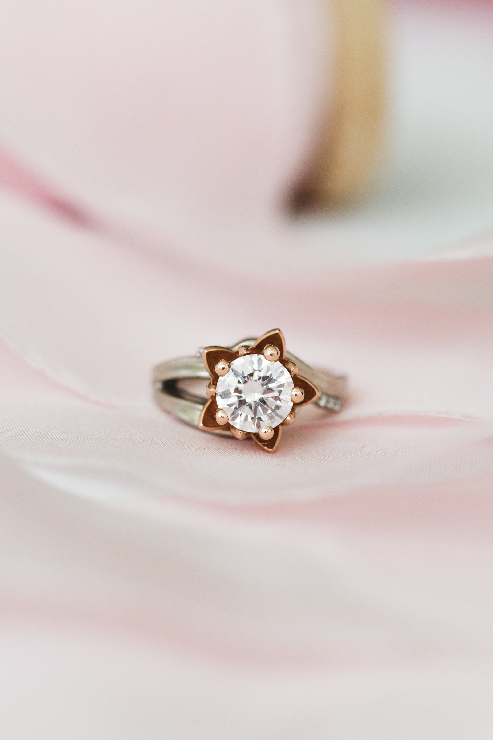 engagement ring by custom made jewelry photographed with pink ribbon