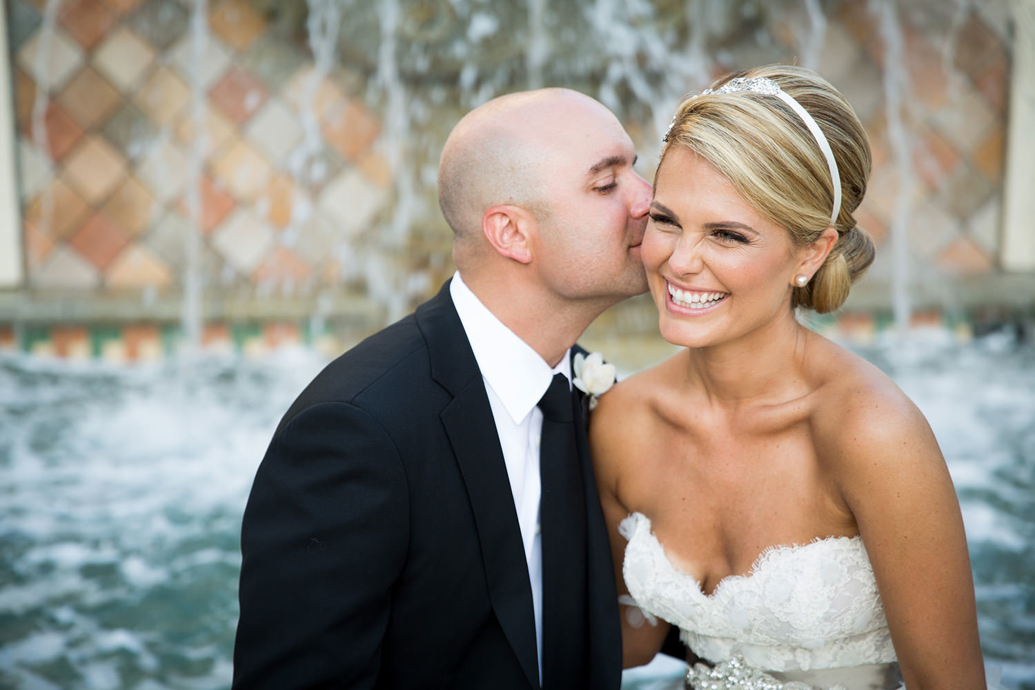 Groom sneaks a kiss in front of the water fountain at St Regis Monarch Beach
