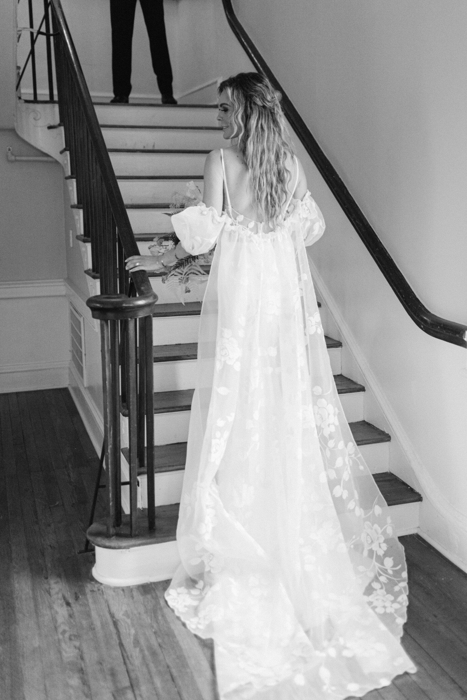 black and white photo of a bride walking up the stairs