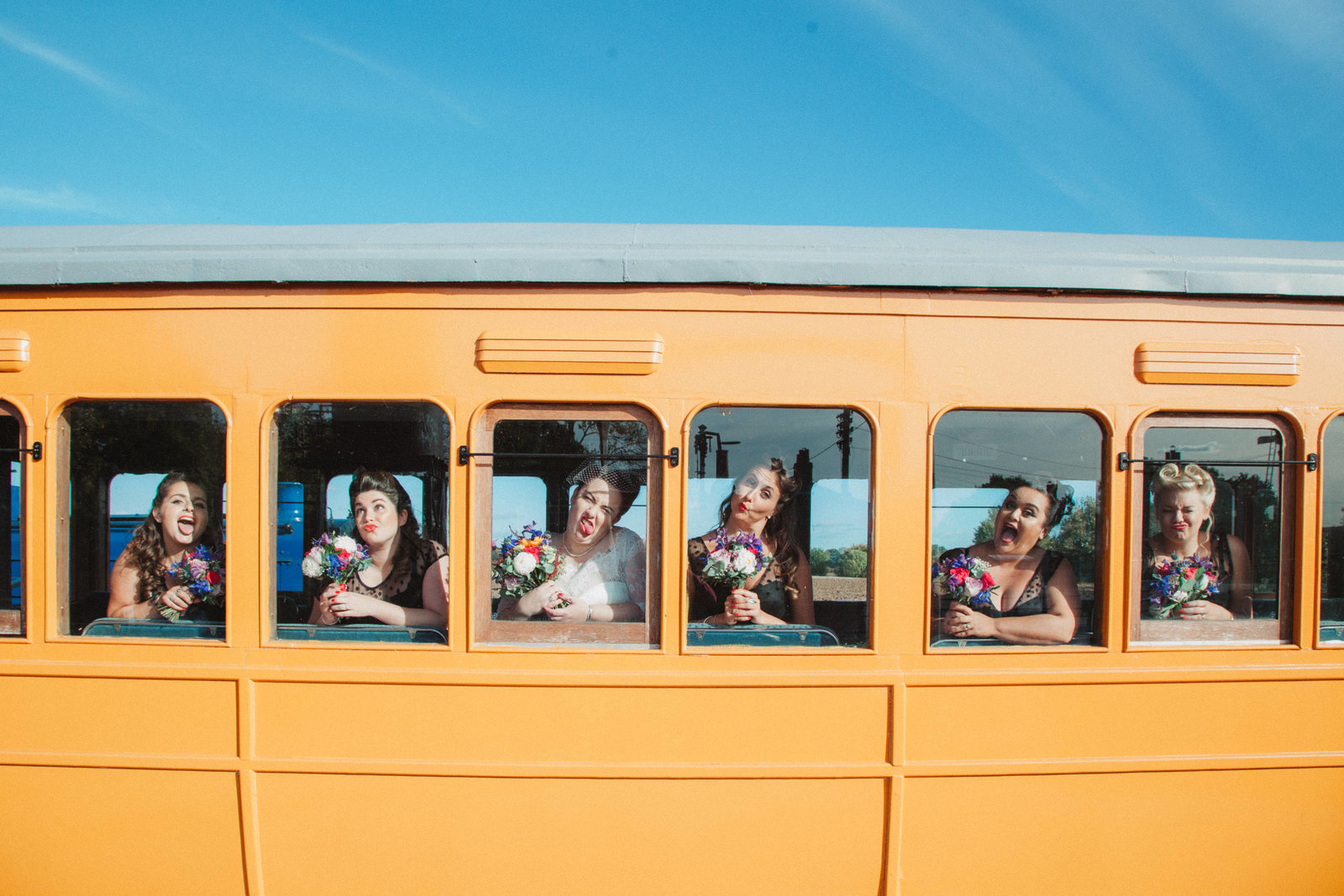 Fun bride and bridesmaids pulling faces in yellow train carriage windows at East Anglian Railway Museum Wedding