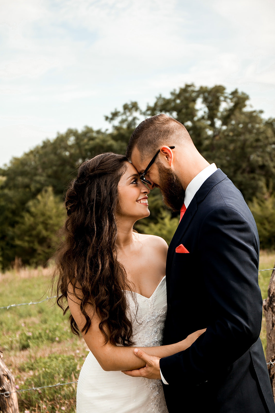 Des Moines Iowa wedding couple foreheads together in the field.