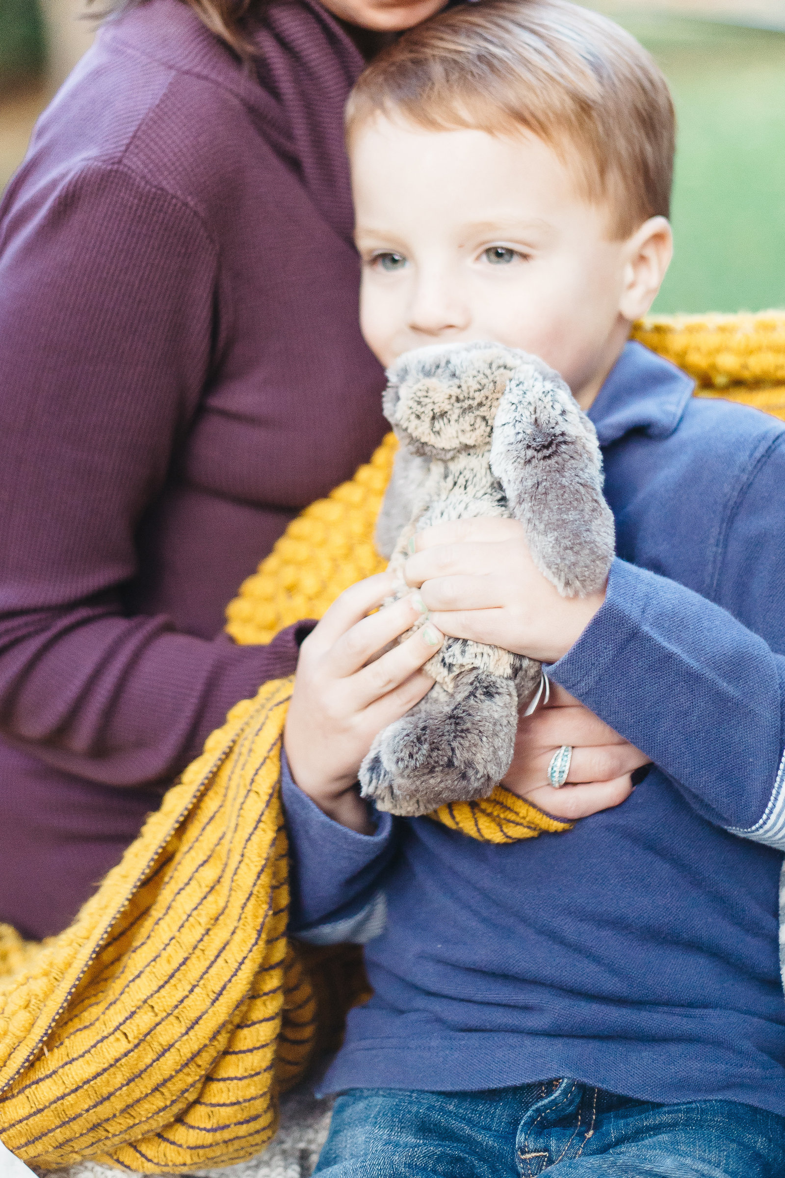 A small boy cuddling a stuffed rabbit in his mother's arms