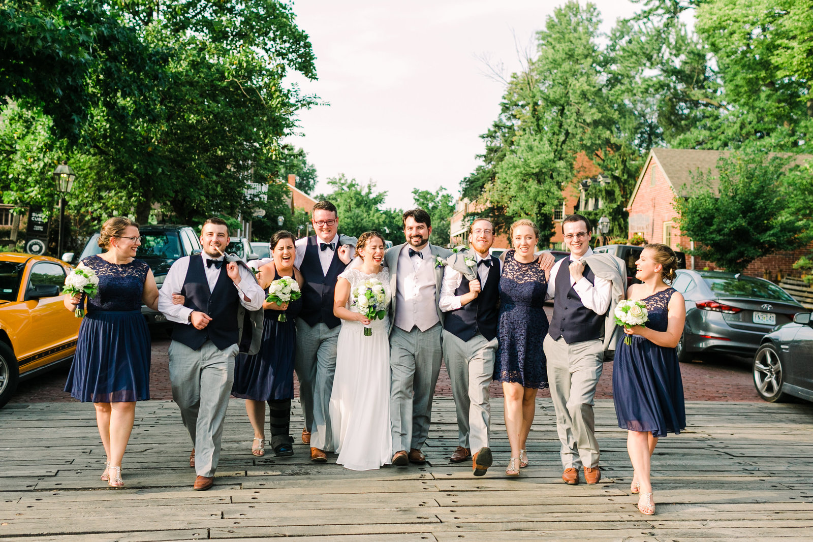 This fun wedding party walks down the street arm in arm down Historic Main Street in St. Charles