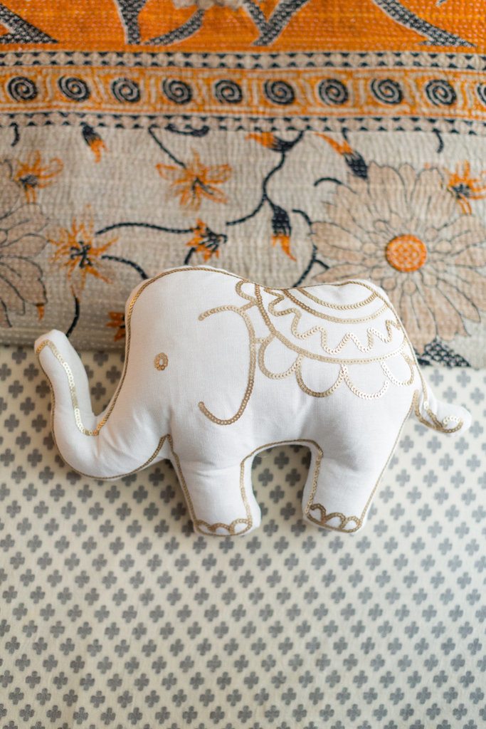A white and gold stuffed elephant on a patterned duvet.