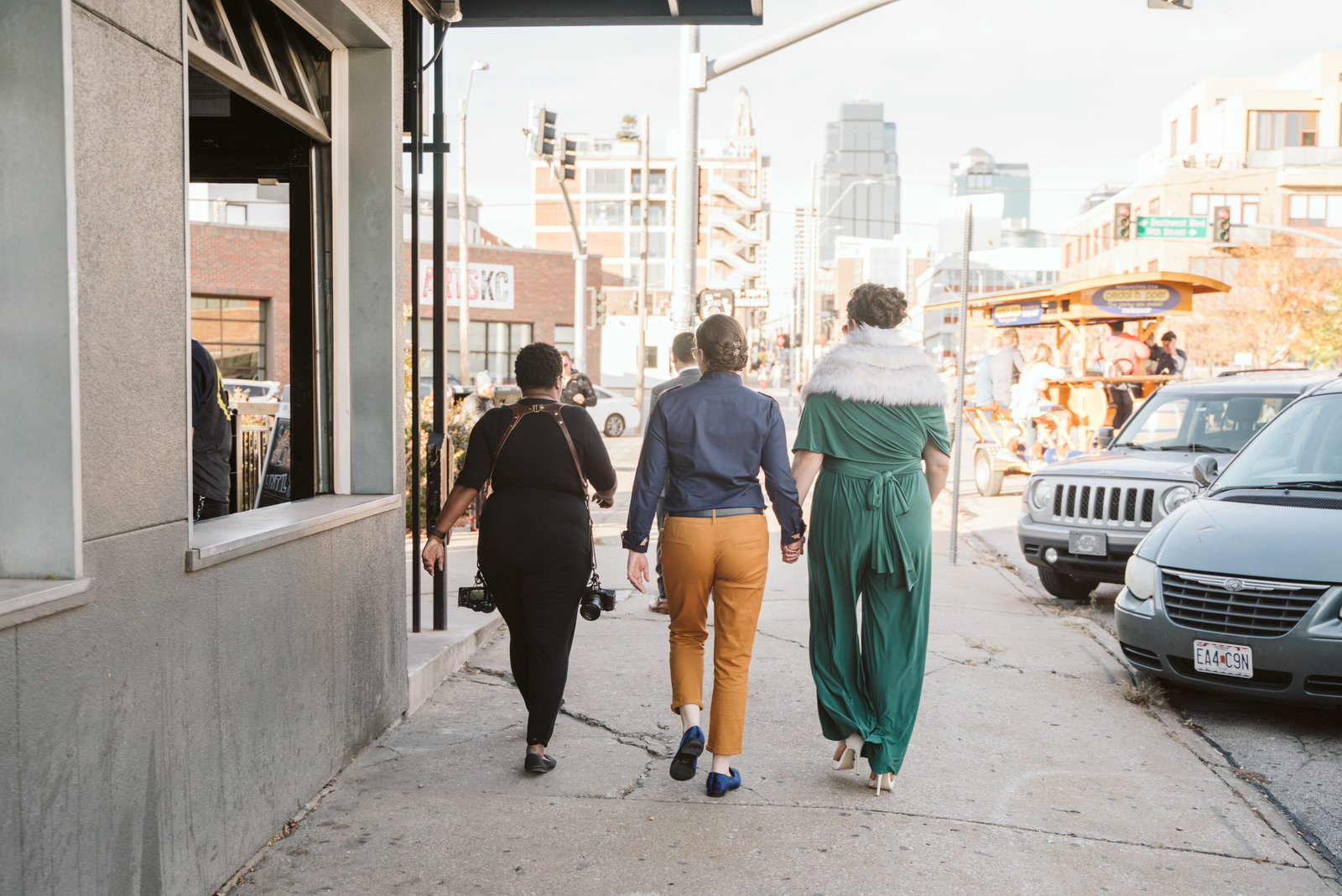 Photographer walking with same sex couple during wedding