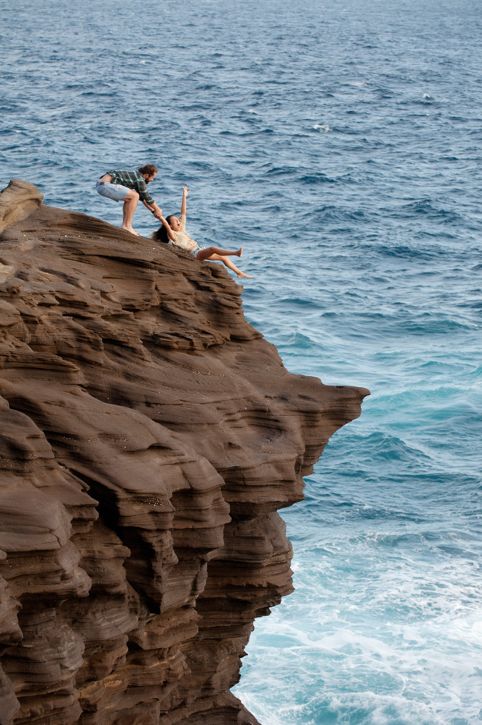 a girl pretends to slide down a cliff into the ocean as her fiance pulls her hand in honolulu