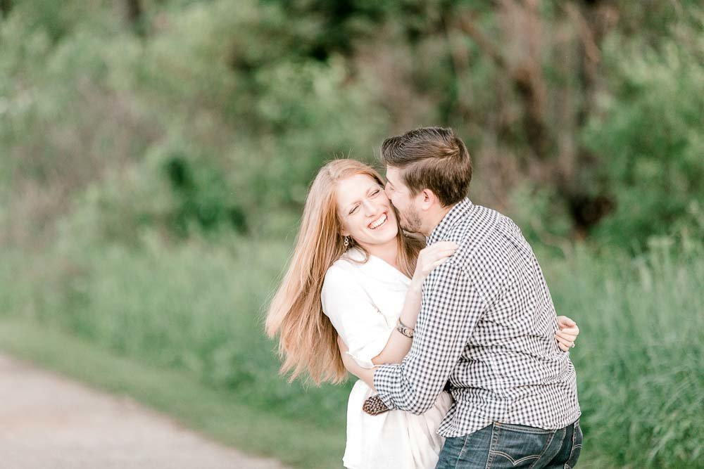 Candid moment of a couple hugging and laughing during their engagement session.