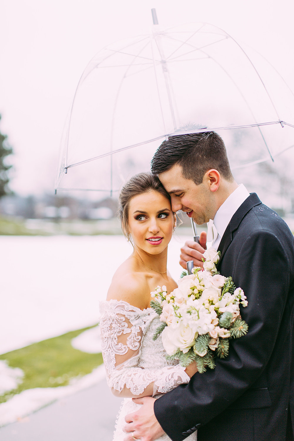 Bride and groom under umbrella in rainy wedding photo by Samantha rice