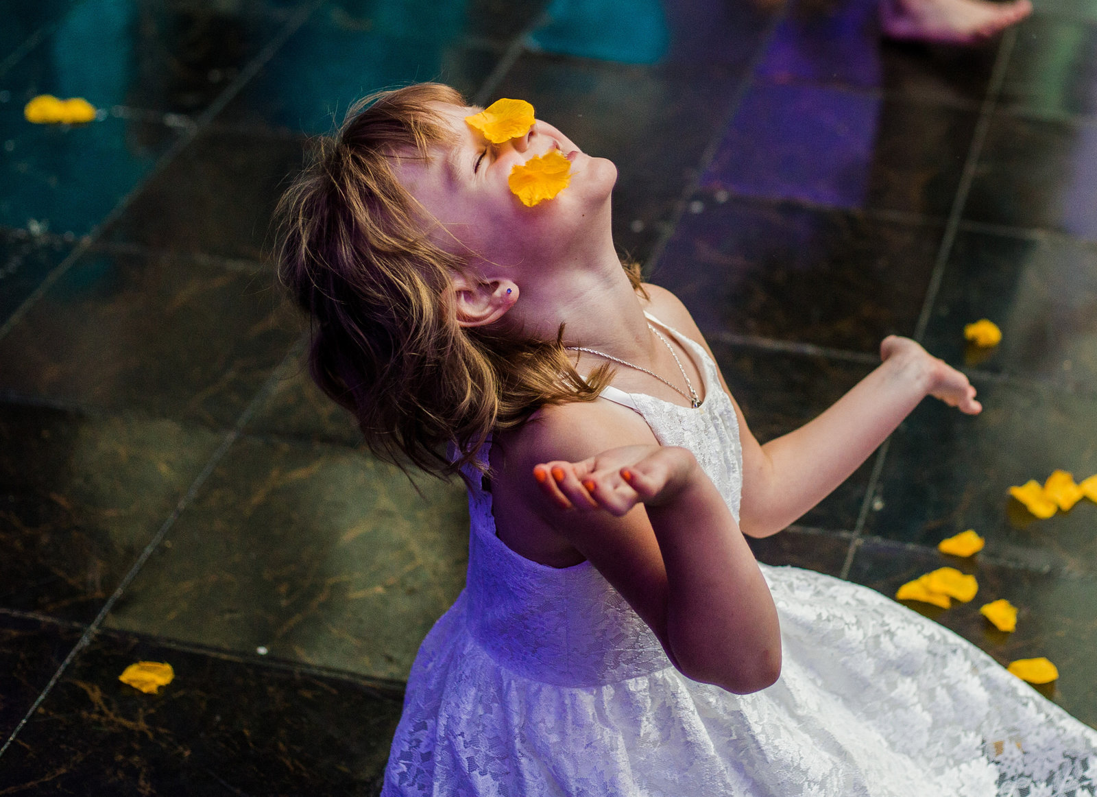 Child plays with flower petals during wedding reception at the Concourse at Union Station