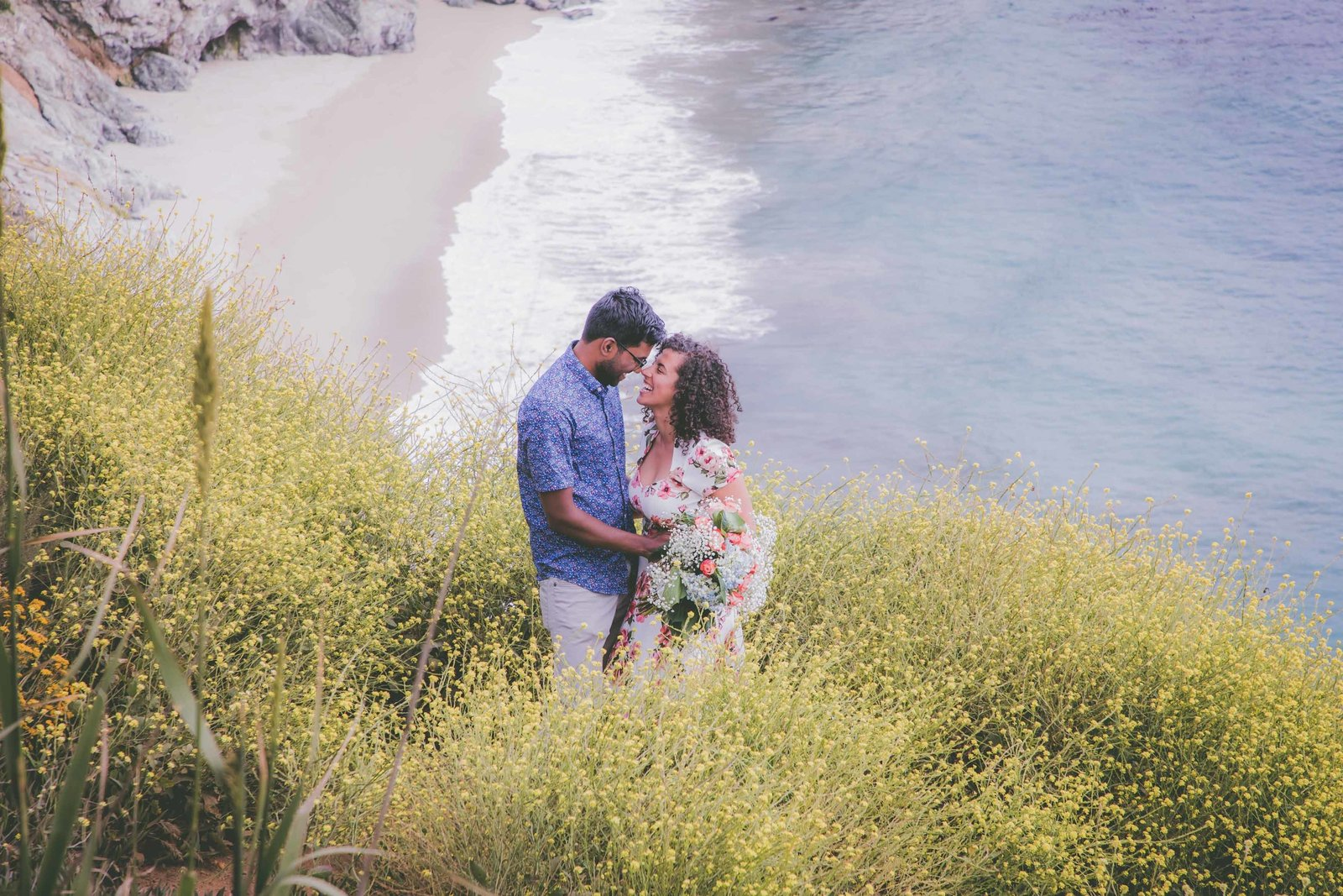 Couple touches foreheads among wildflowers with ocean view in Big Sur.