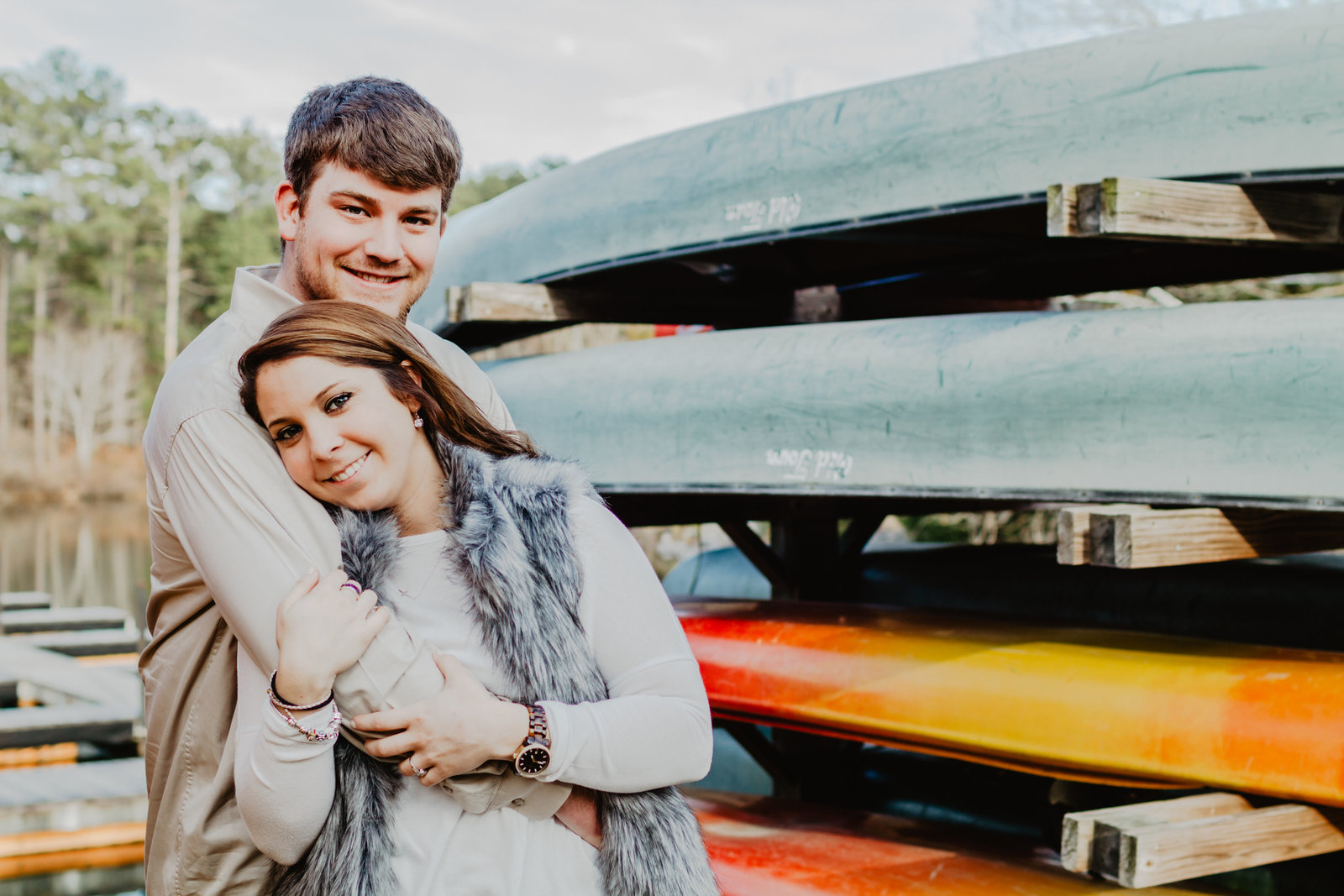 Standing by the canoes at Oak Mountain State Park, soon to be bride wraps her arms around her soon to be grooms arm.