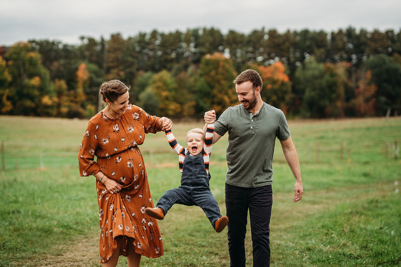 pregnant couple swings toddler boy in air during maternity pictures
