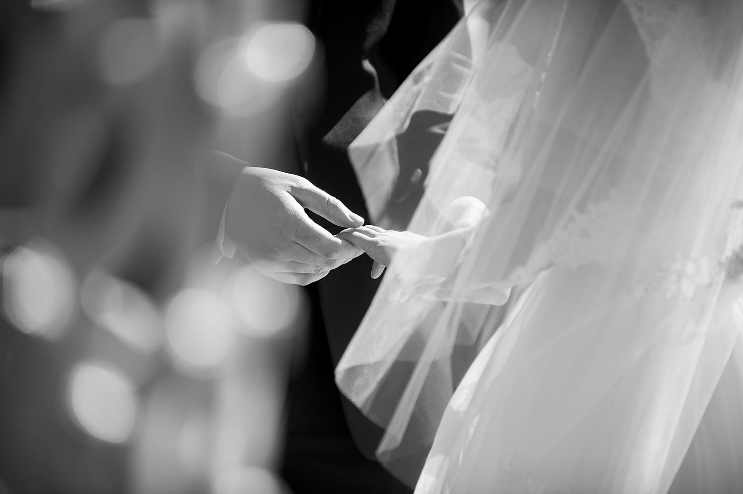 groom putting on brides wedding ring