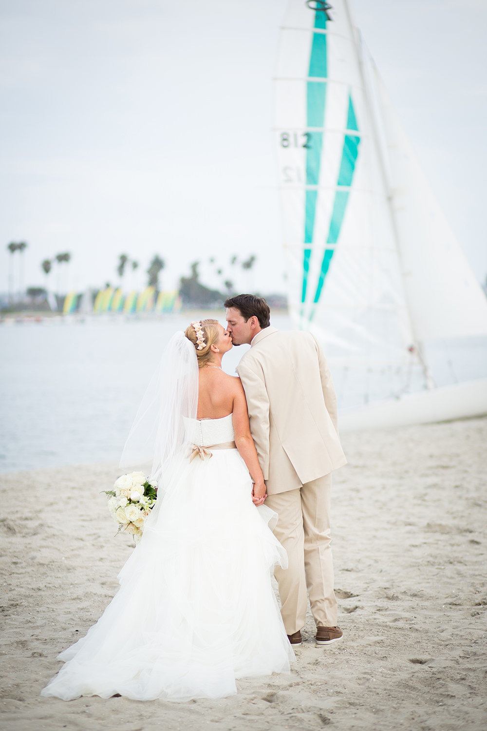 couple kissing with sailboat in the background