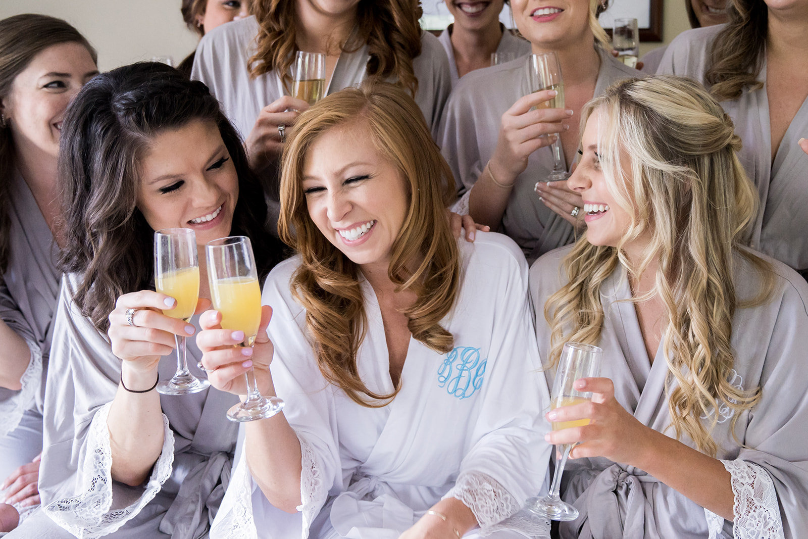 bride drinking mimosas with bridesmaids