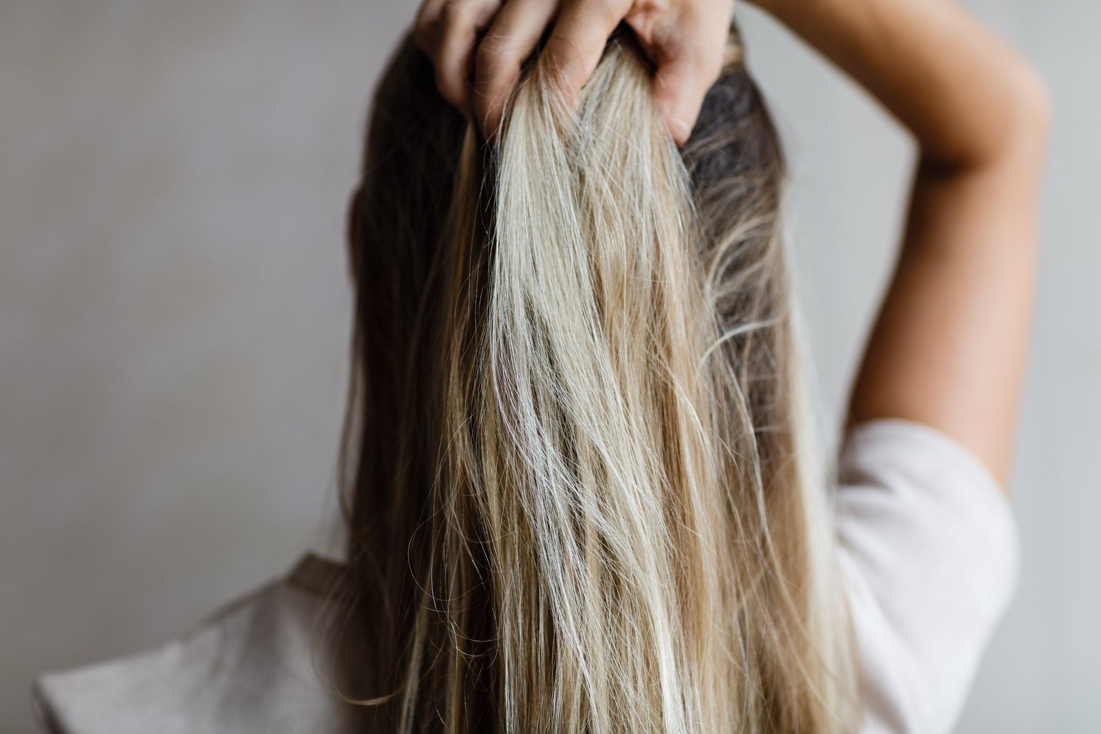 nominated-woman-holding-hand-her-long-blonde-hair-view-from-behind-coloration-ombre_t20_LOondo
