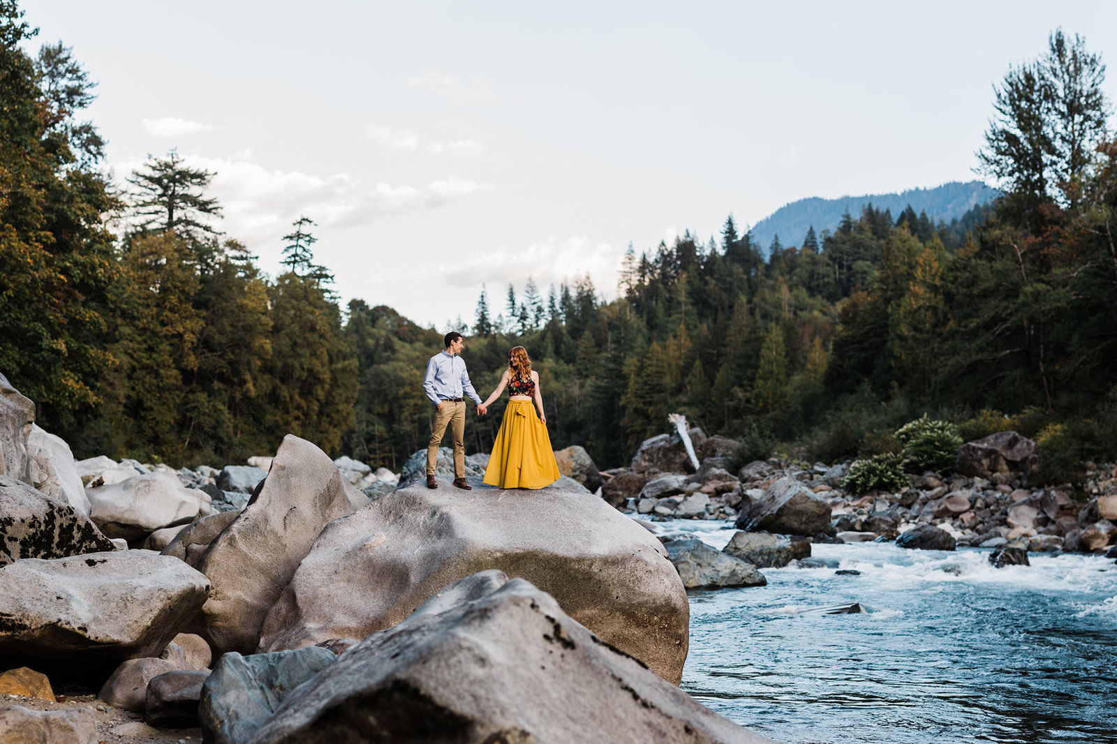 a woman in a flowing mustard color dress and her partner stand on a rock in the middle of a river in the cascade mountains during their adventure engagement session with amy galbraith