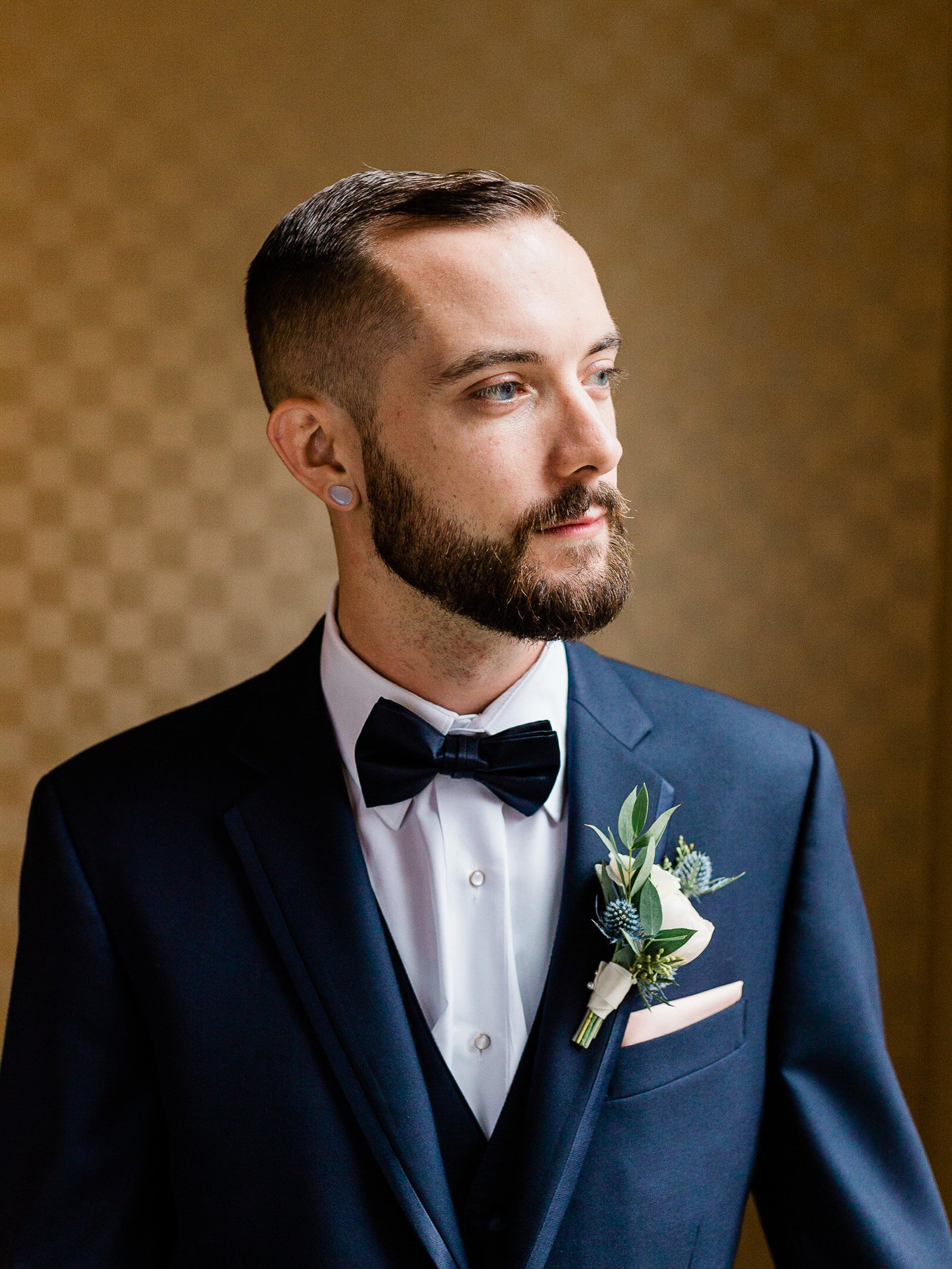 Groom in a navy suit with bow tie, modern boutonniere in kimpton hotel Monaco room