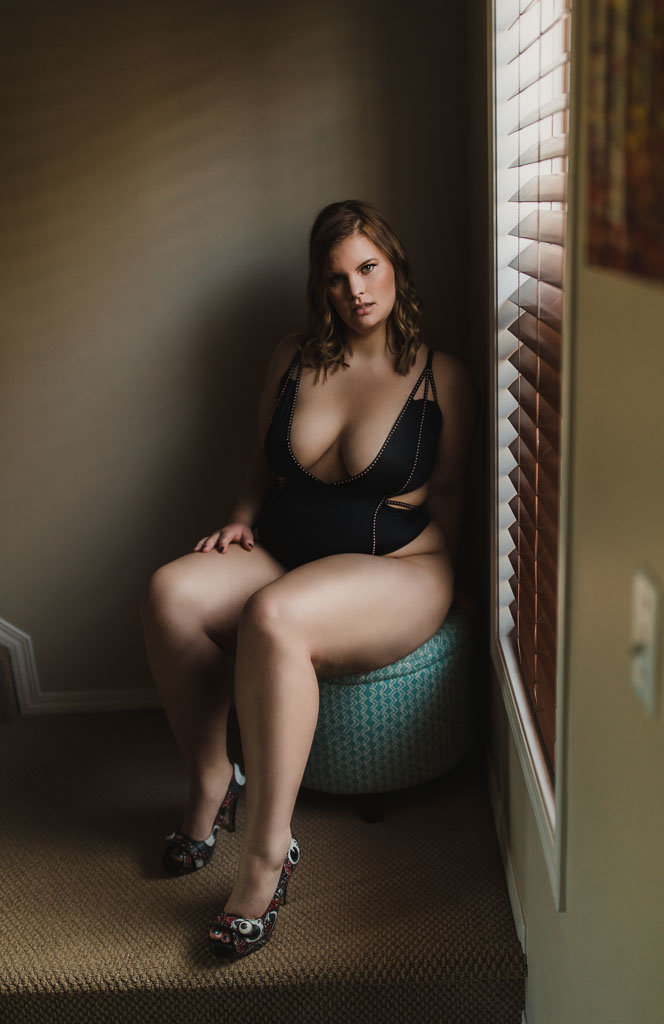 Woman sitting on teal stool in black bodysuit