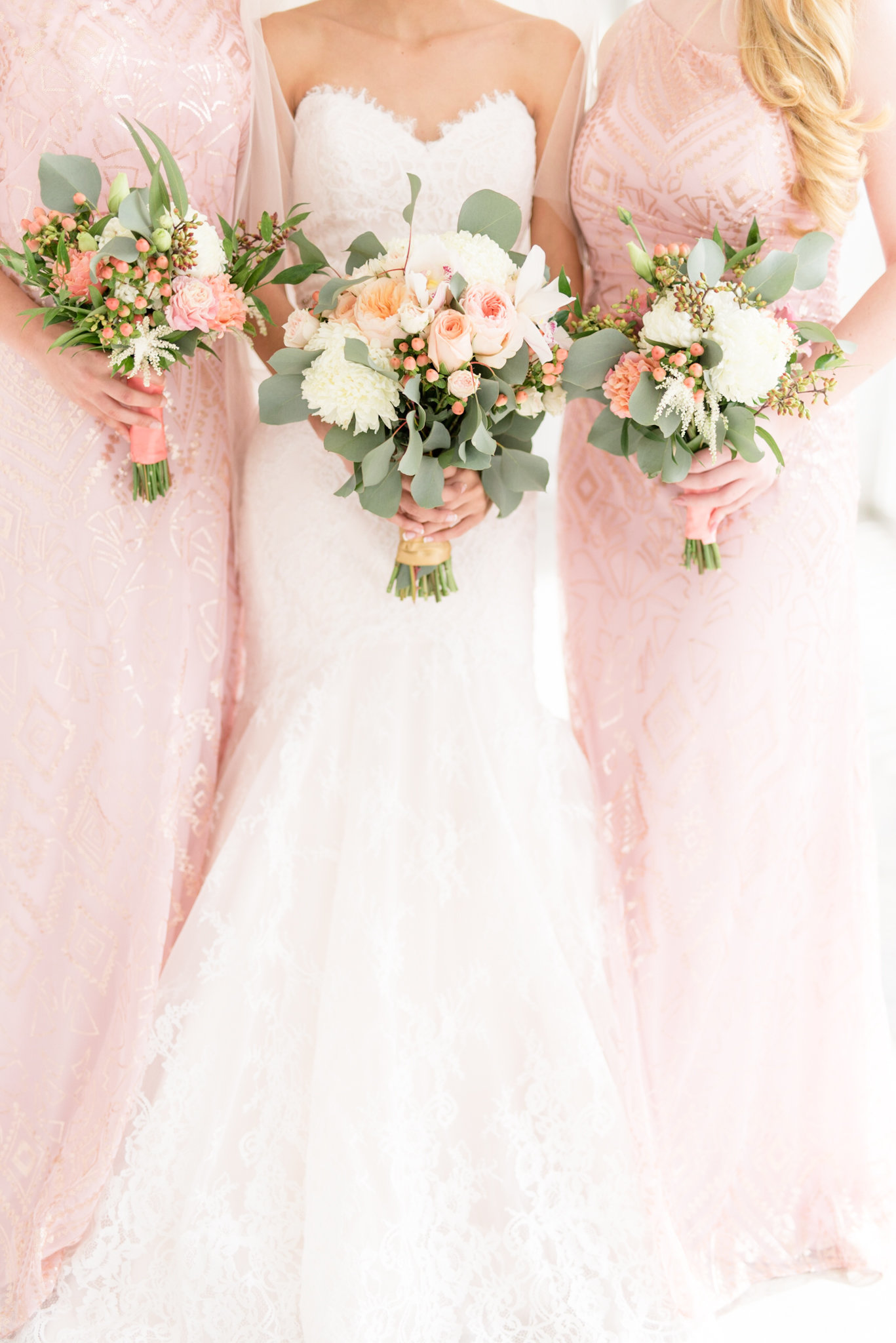 Bride and Bridesmaids hold pink bouquets.